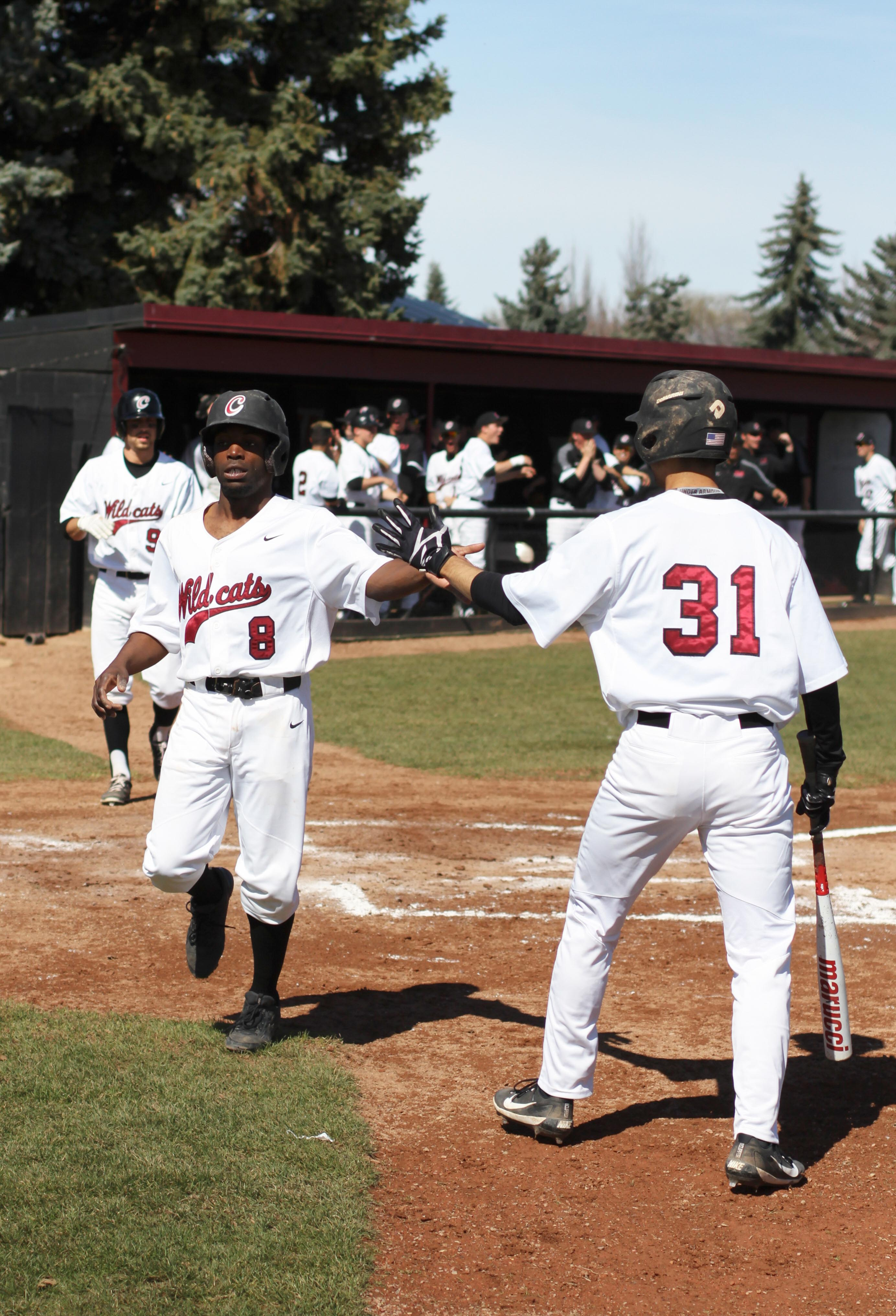 #8 Rory Graf-Brennen hi-fives #31 Yi-Fan Pan after rounding the bases.