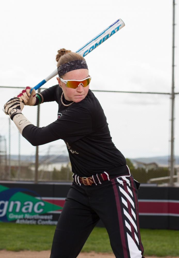 Kailyn Campbell takes a swing at a photoshoot with a photographer at Frederick Field.