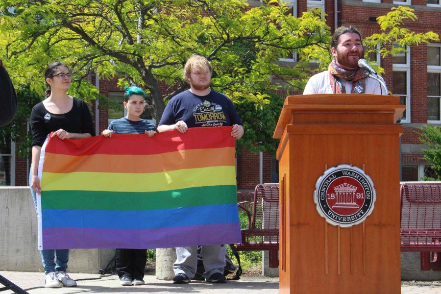 Patrick Carpenter speaks at the ceremony while other EQuAl students hold the flag that is now flying above Barge Hall.