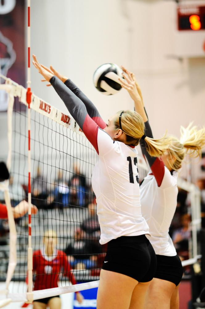 Now graduating Kiah Jones (13) and her teammate going up for a block during a game.