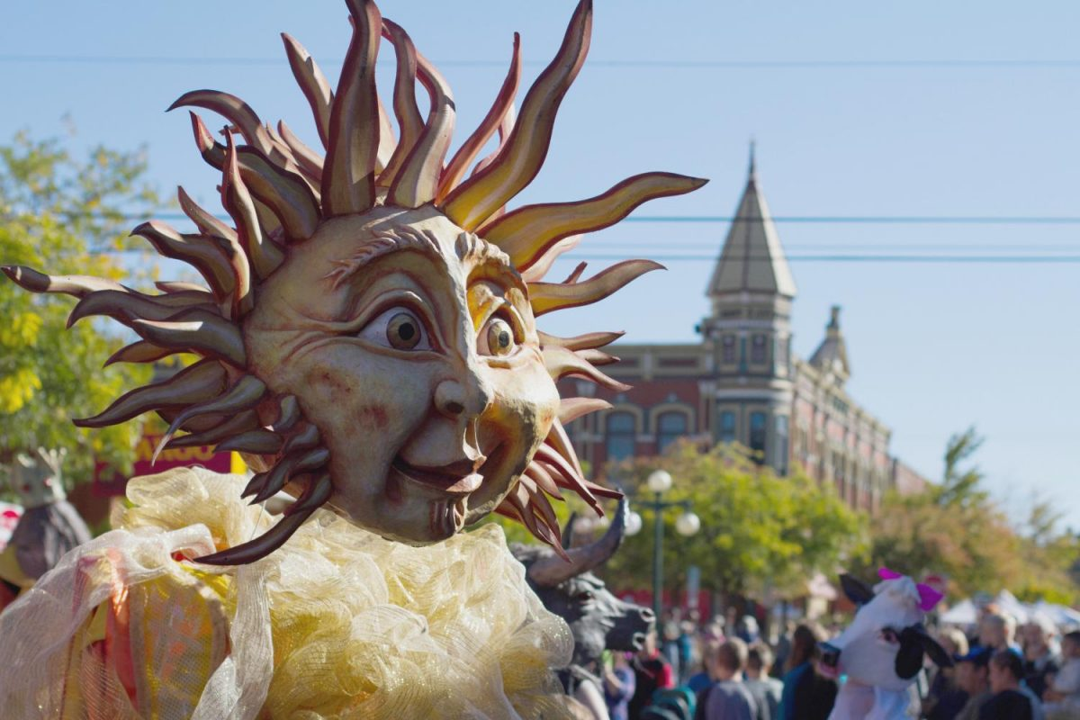 The+sun+head+body+puppeteer+walks+in+the+Arts+Parade+during+the+festival.
