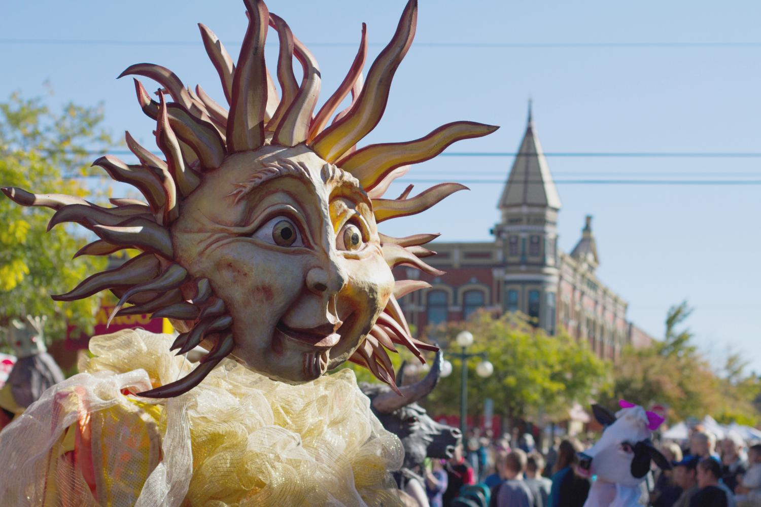 The sun head body puppeteer walks in the Arts Parade during the festival.