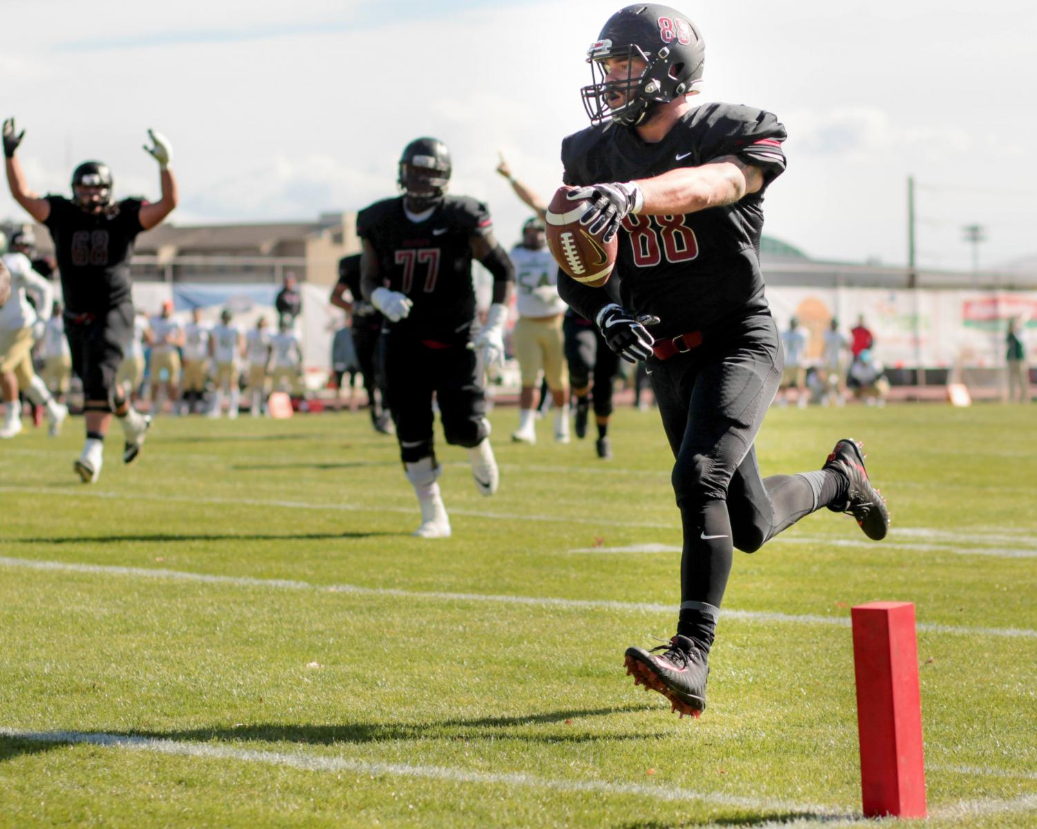 Dillon Sugg runs for a touchdown at during a home game while his teammates celebrate behind him.