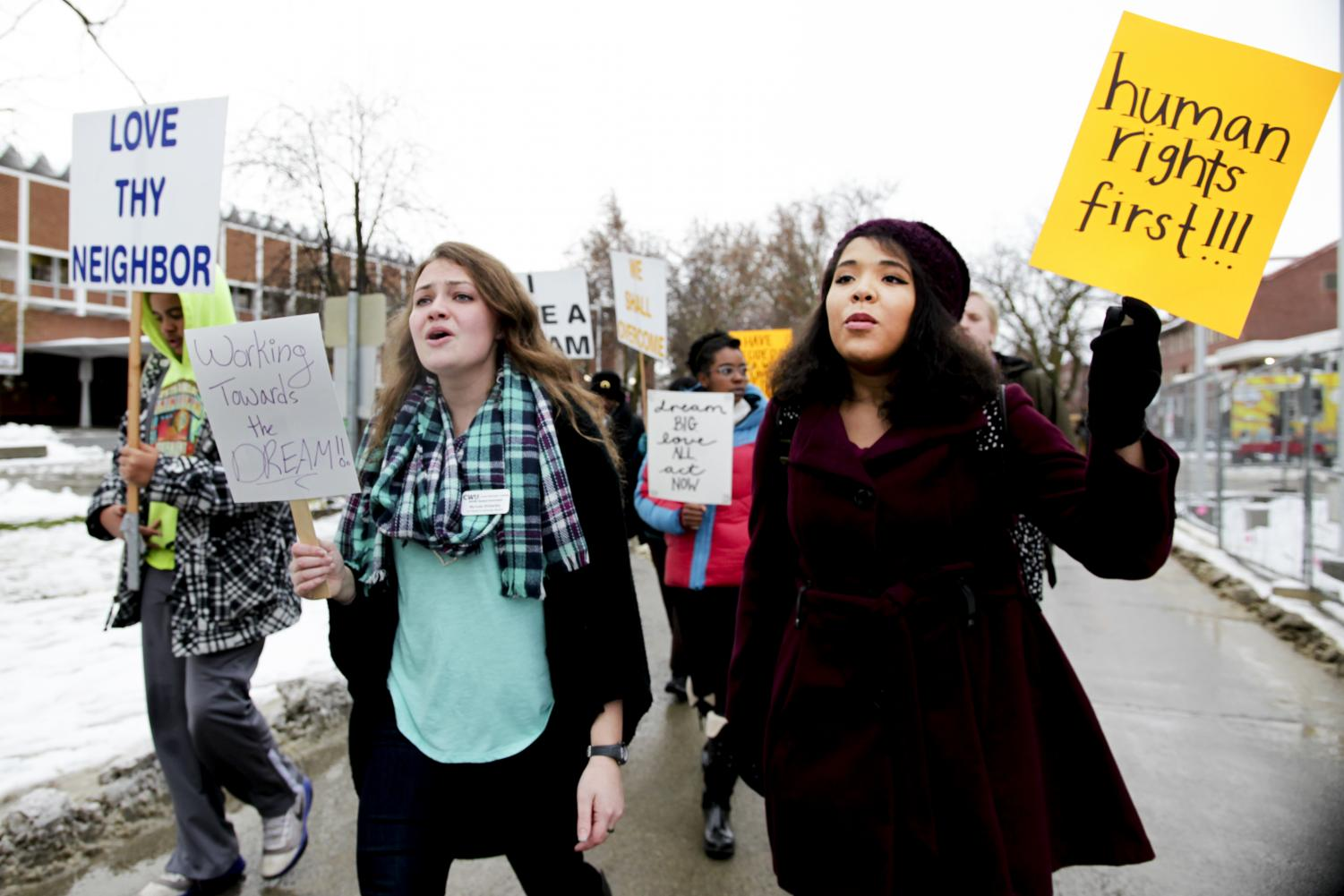 Myrinda Wolitarsky, left, and a fellow marcher hold their signs up high while walking up Walnut Mall.