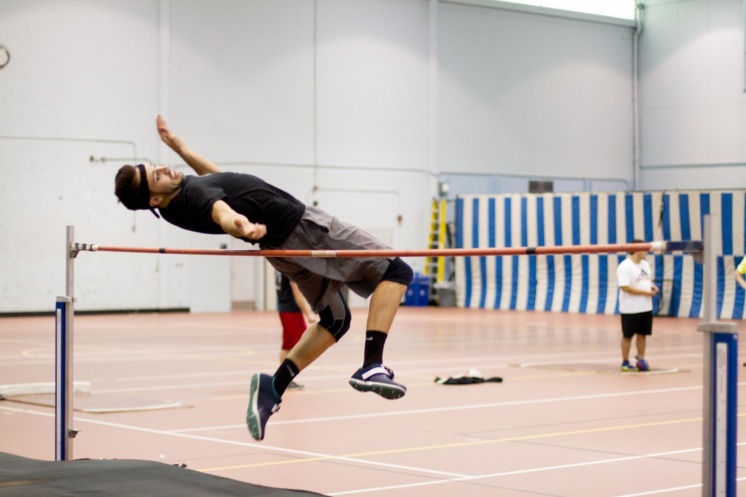 Nick Bullo clears the bar while practicing for high jump during an indoor practice session.