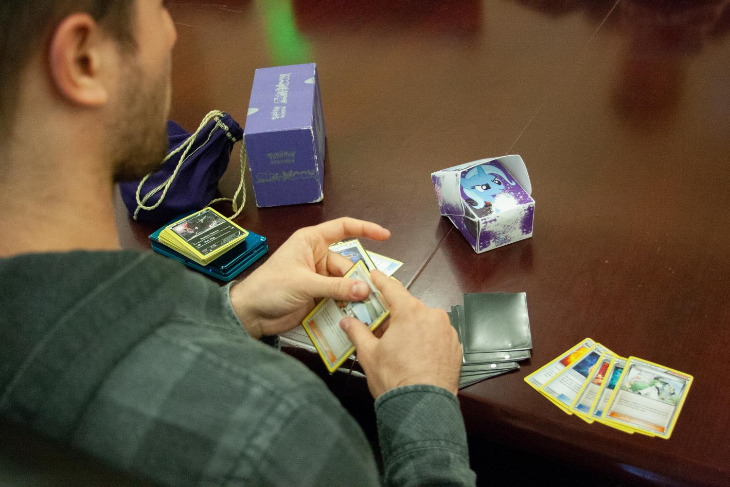 Pokemon Club Member Boewen Piotrowsk puts cards into protective sleeves before an in-house game.