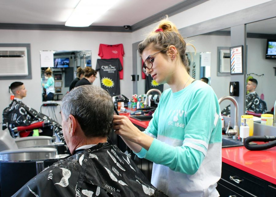 Leah Lewis trims Tom Rosser's hair at the CWU Barber Shop.
