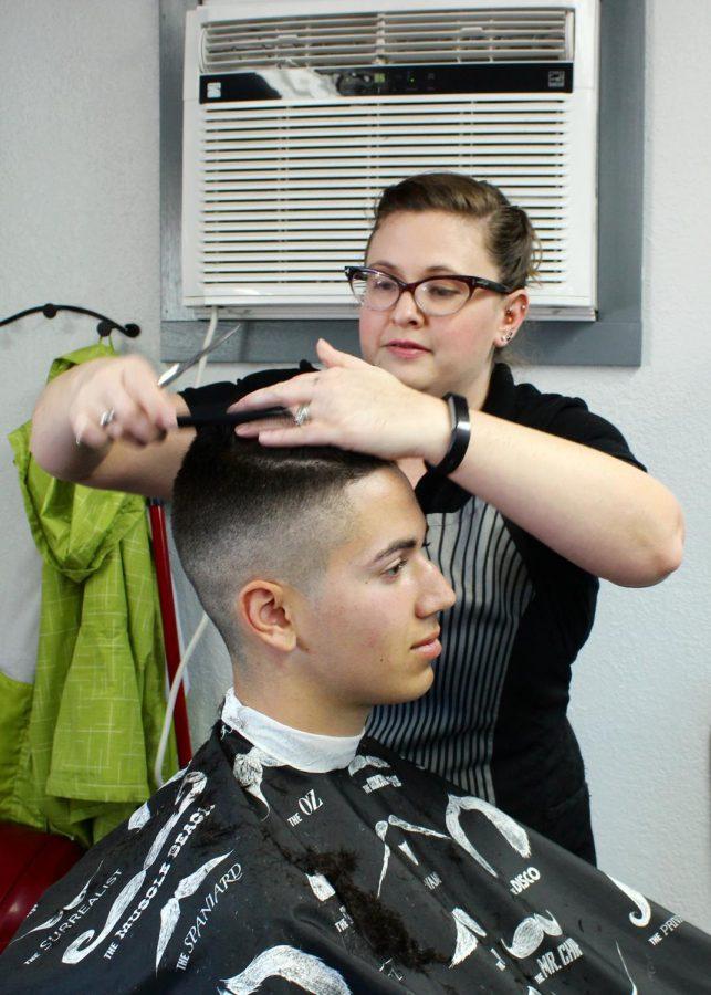 Caelsey Schmidt clips Derek Davis's hair at the CWU Barber Shop.