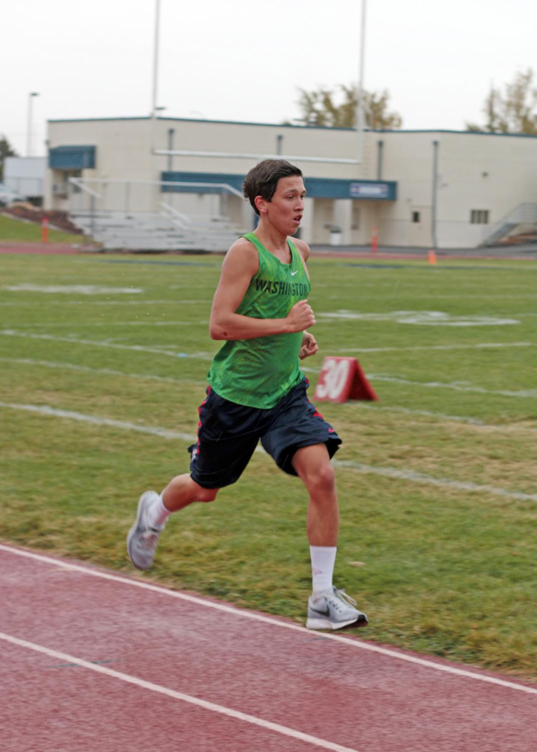 Turlan Morlan times his 400m pace at cross country practice.