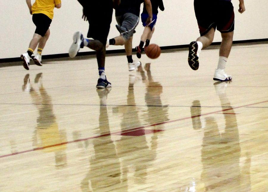 CWU students chase after the ball during a competitive game of pick-up basketball.