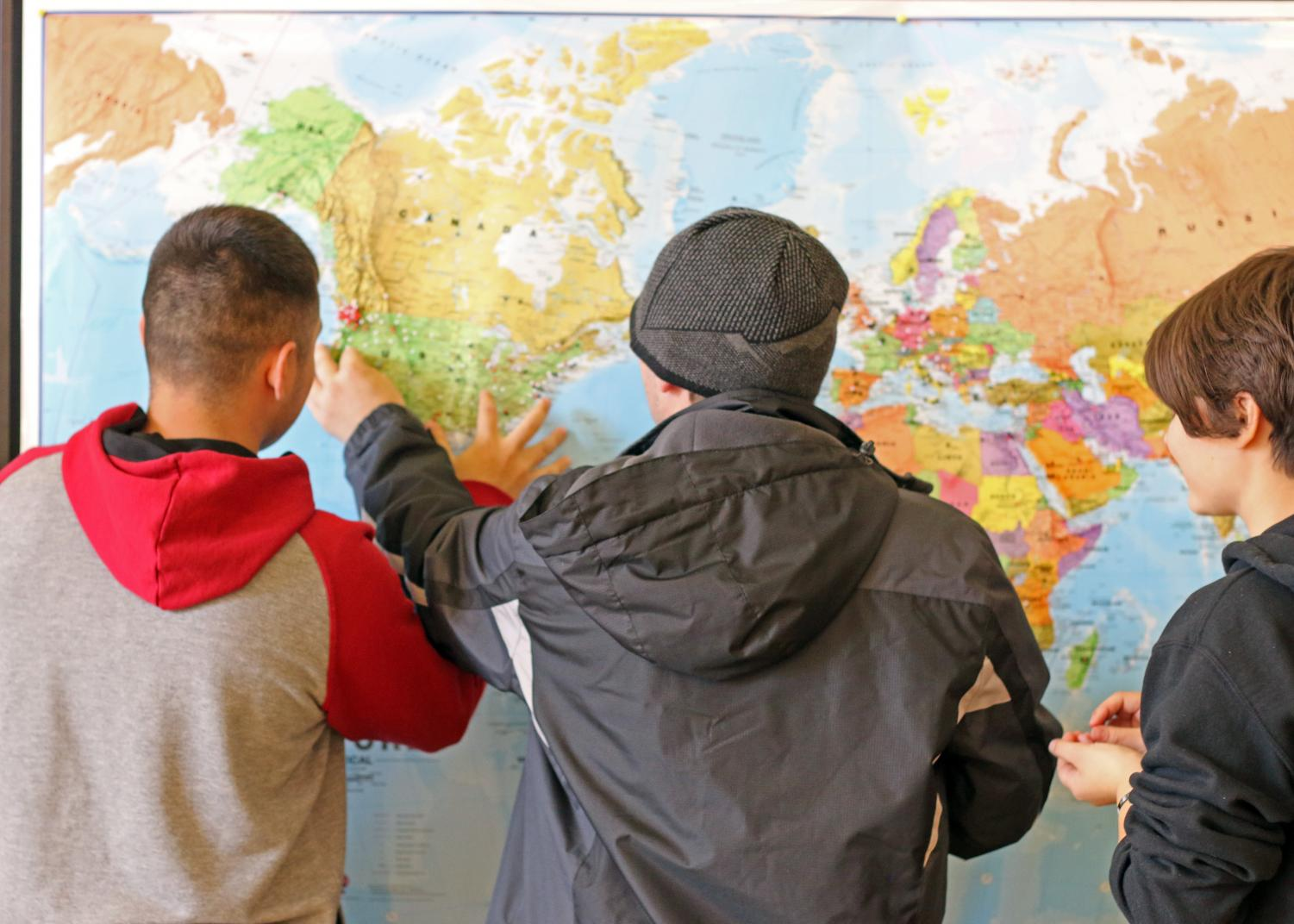 (From left to right) Pablo Ruelas, Job Place and Claire Olney have fun with the world map in the SURC by marking places they have been. have lived, and would like to go.
