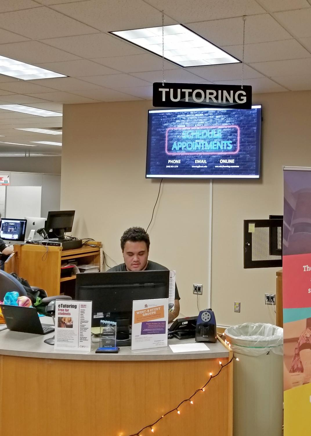 Front Desk Office Assistant Sione Sausau helps students check in for tutoring.