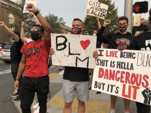 Protesters against police brutality hold up Black Lives Matter signs they made.