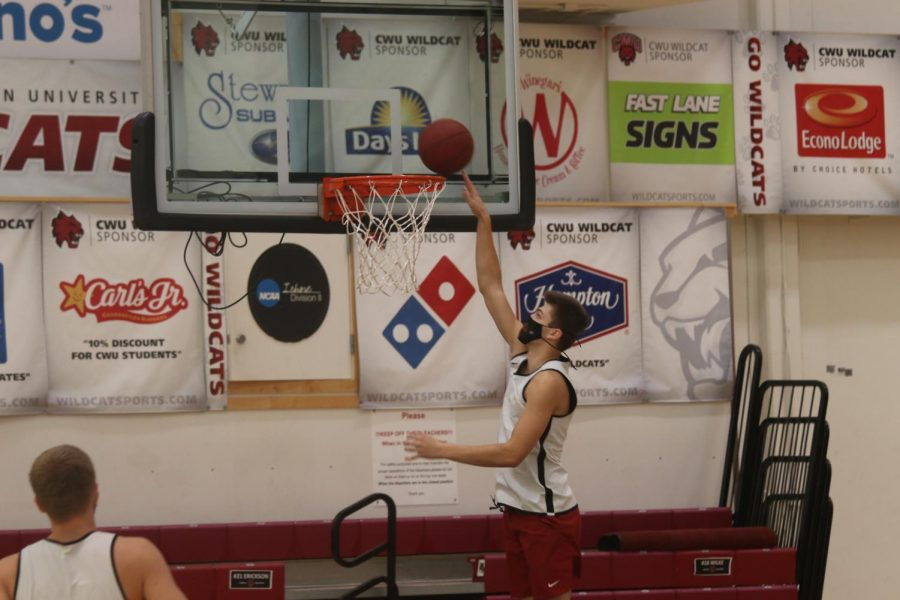 Freshman Forward Gaige Ainslie doing a lay up drill at practice.