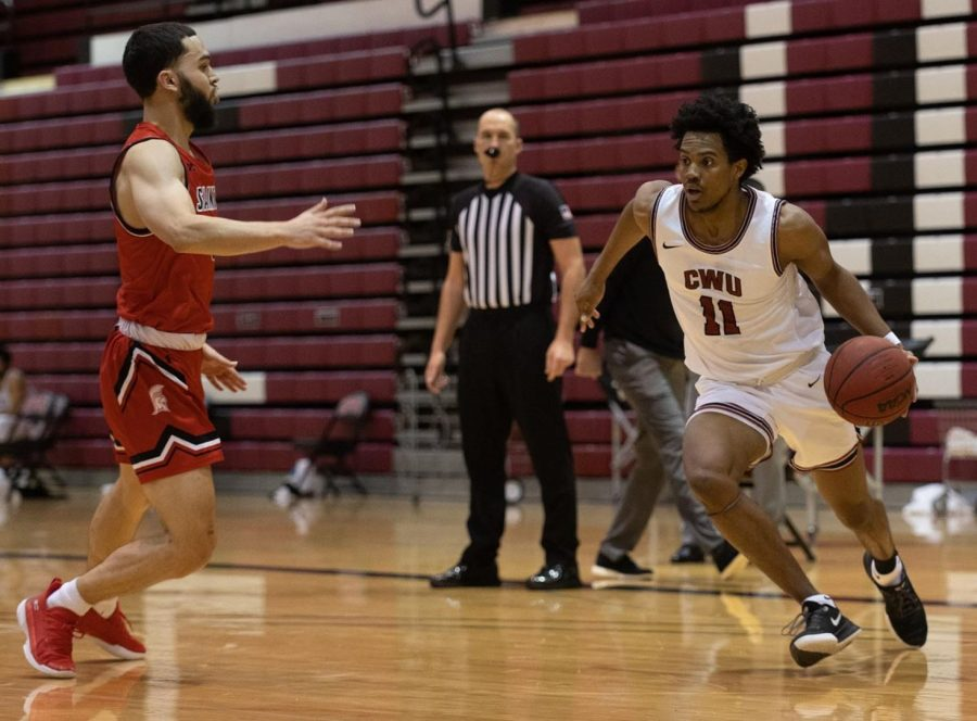 Xavier Smith (right) drives base line to score a basketball in last Saturday's game.