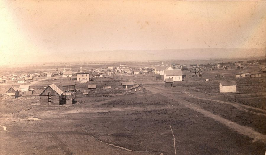 Aerial from Craig Hill before July 4, 1889: This photograph depicts the young city of Ellensburg, taken before the fire from Craig's Hill, between 3rd Avenue (to the left) and 4th Avenue (on right). The big white building slightly right of center is the Johnson House (it looks like a three-tiered cake). That building was located on the northwest corner of West 4th Avenue and North Pearl Street (today where Rotary Pavilion is), and was where patrons attending a dance first noticed the J. S. Anthony building on fire.