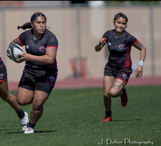 Mae Sagapolu (left) and Maryjane Pasioles attempt to score a try.