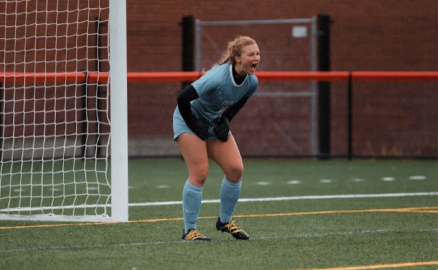 Emily Thomson celebrates after she stops a forward from scoring a goal.