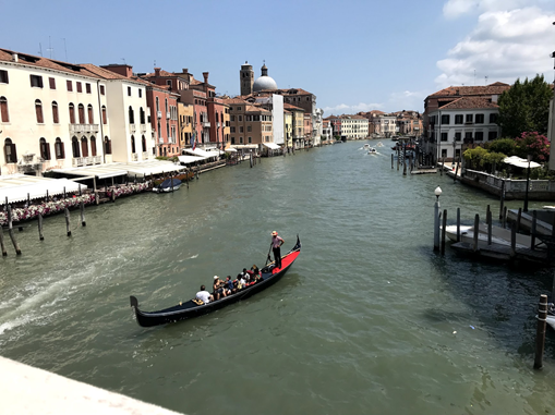 A view from the Rialto Bridge in Venice, Italy of a gondola(a long boat) with several passengers taking a ride.